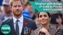 Меган прикалывает золотой значок к куртке принца Гарри