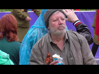 Мужчина кушает мороженое на 9 мая и слушает музыку