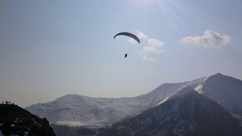 Парапланерист красиво пролетает над горными вершинами на Кавказе (HD)