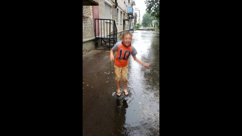 Саша в дождь прыгает по лужам
