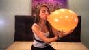 Fun girl blows up an orange balloon until it bursts