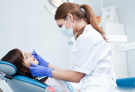 Зубной гигиенист, чистящий зубы человека.