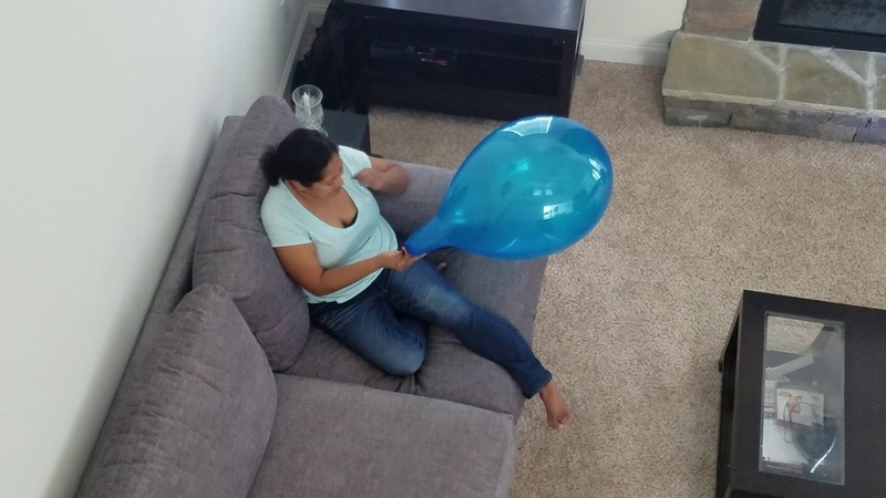 Girl blow to pop blue balloon