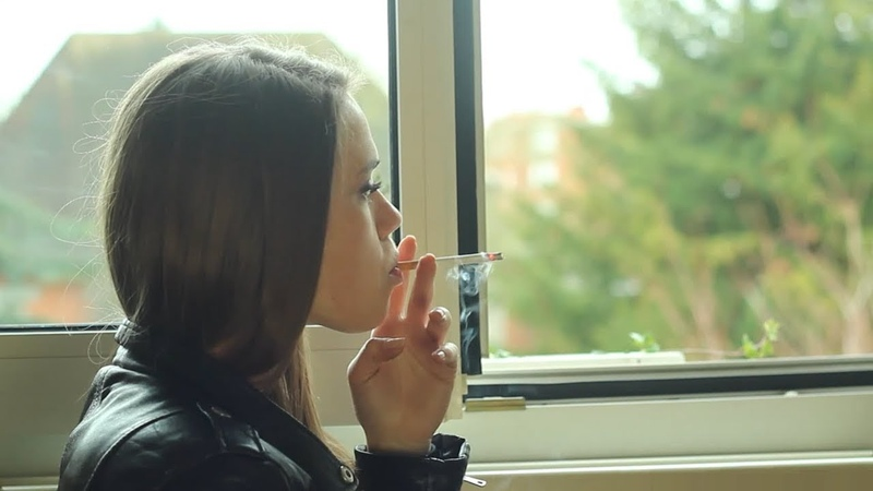 Pretty girl smokes a long cork cigarette