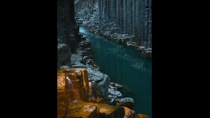 Вода течет через базальтовые колонны Исландии