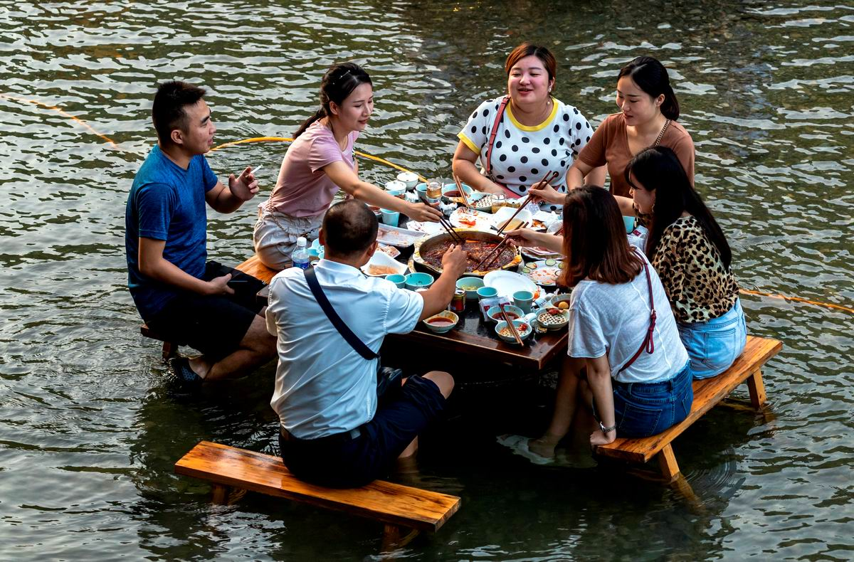 Сидя за столиком по колено в воде: Простой китайский пикничок