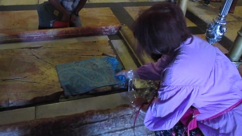 Карима освящает шаль на Камне Миропомазания.