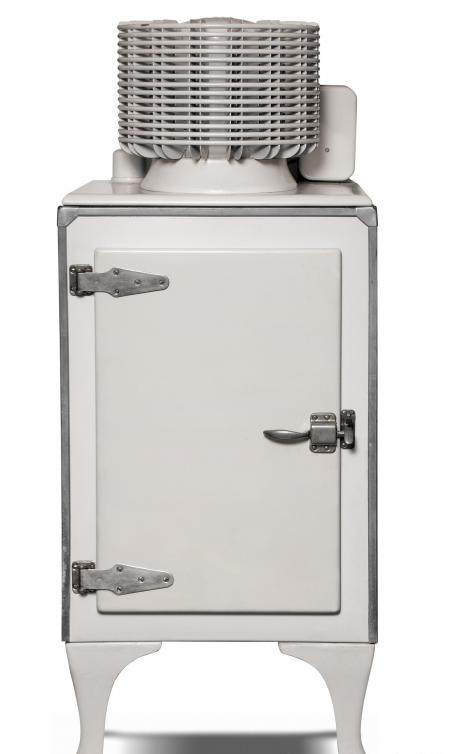 Старинный холодильник с компрессорным агрегатом сверху.