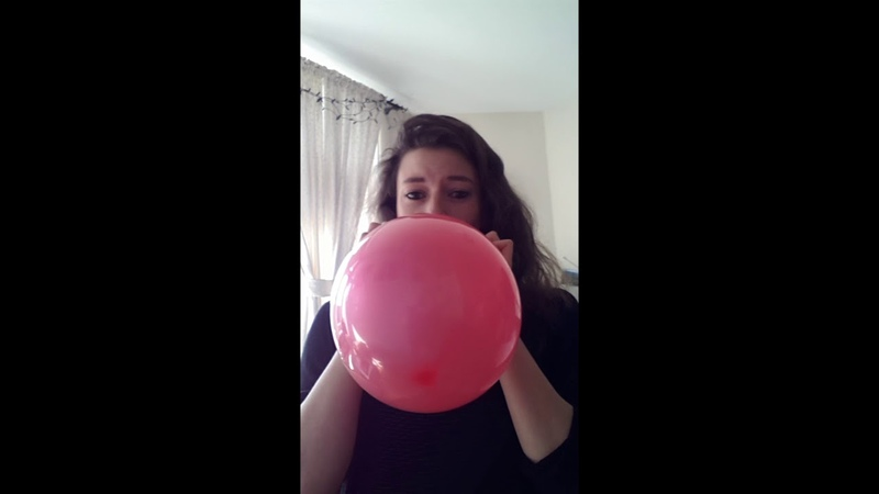 Girl blows up a big red balloon until it pops loudly