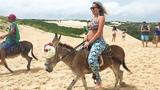 Gabriela cavalgando de jegue nas dunas de Natal-RN