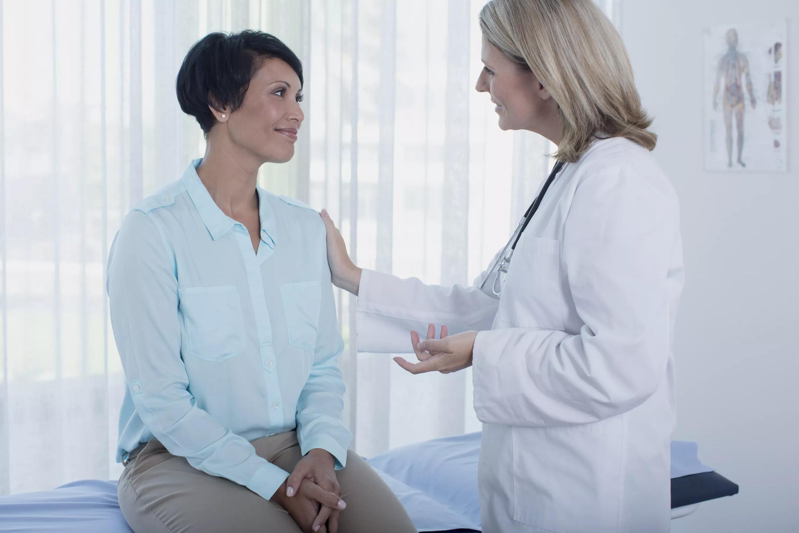Улыбающиеся женщина-врач разговаривает с пациентом в офисе про антидепрессанты.
