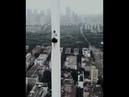 Бесшабашная девушка без страховки залезла на шпиль небоскреба в Китае