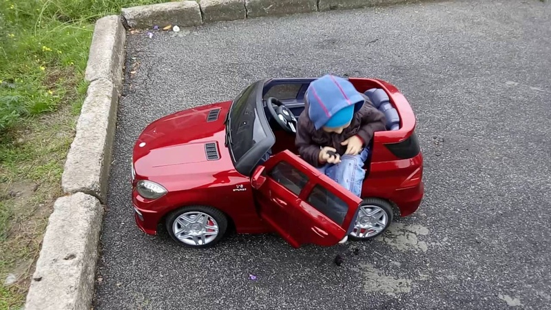 Маленький мальчик катается на детском электромобиле