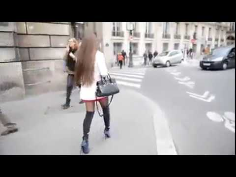 Girl in pantyhose and boots walking on the street