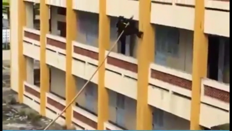 Vietnamese police officers scaling a building wall with a pole
