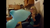 Blonde girl blowing up a giant mouse ear balloon until it pops