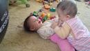 Дочки двойняшки играют друг с другом и улыбаются