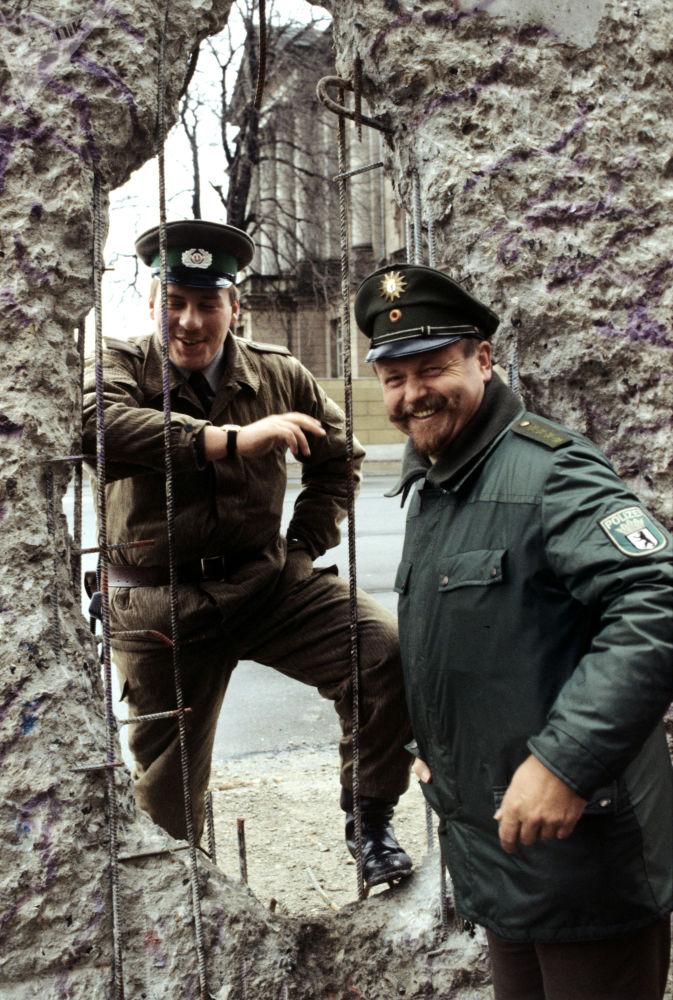 Пограничник ГДР и полицейский ФРГ у Берлинской стены. Берлин. 1990 год.