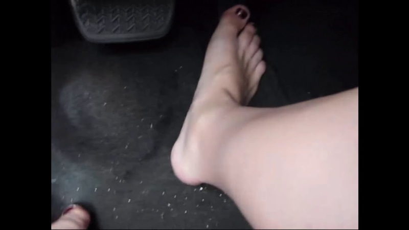 Woman car driving with naked legs and feets.