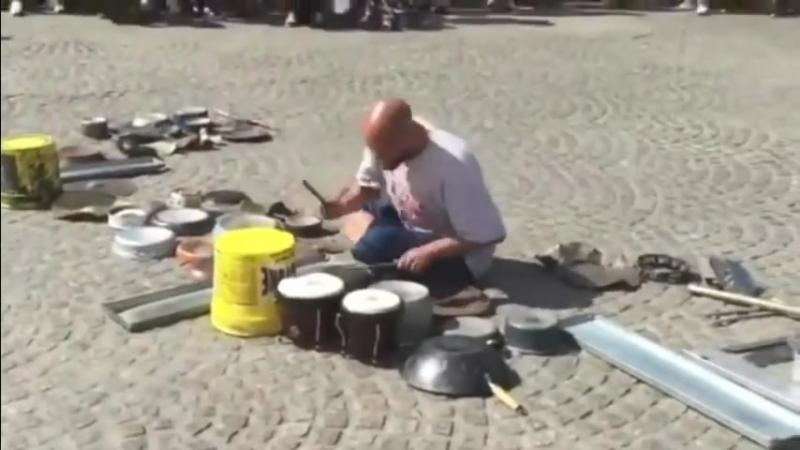 Уличный барабанщик играет на на кастрюлях трубах тарелках в Амстердаме