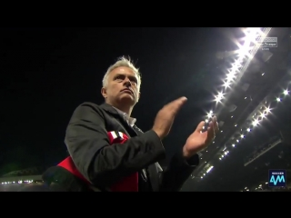 Mourinho picks up a United shirt and scarf, puts it under his arm and applauds the Stretfo