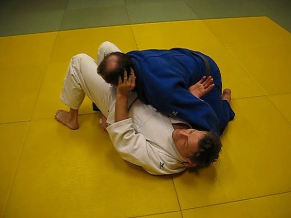 Уход от удержания поперек с отталкиванием головы и защитой ногами.