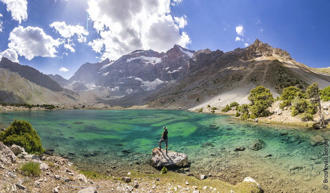 парень на обзорной площадке у озера с видом на снежные горы