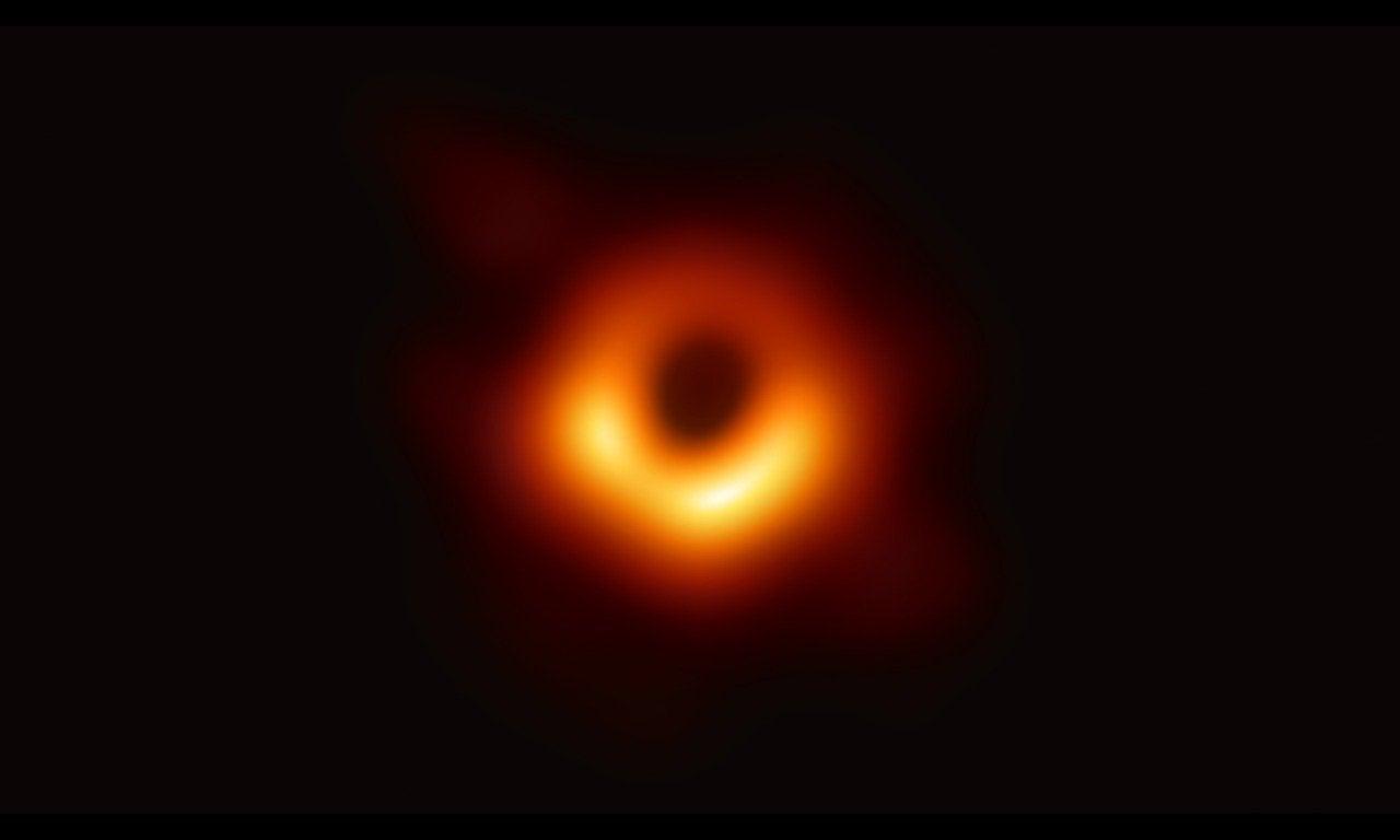 Сверхмассивная черная дыра в обрамлении светящегося излучения и материи.