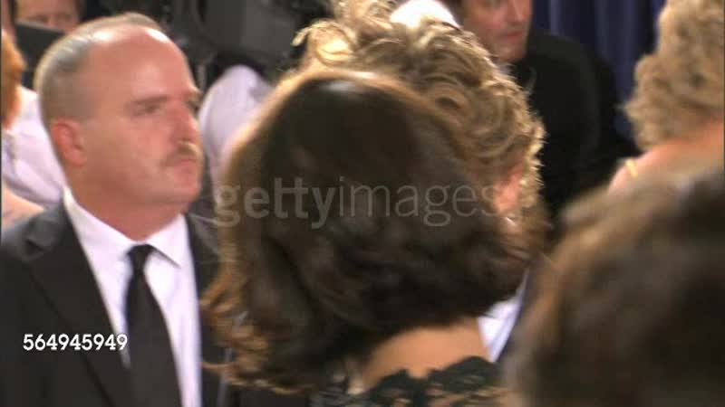 2009 GOLDEN GLOBES AWARDS RED CARPET: CU through crowd- Simon Baker staring into woman's face (back view) intently, listening