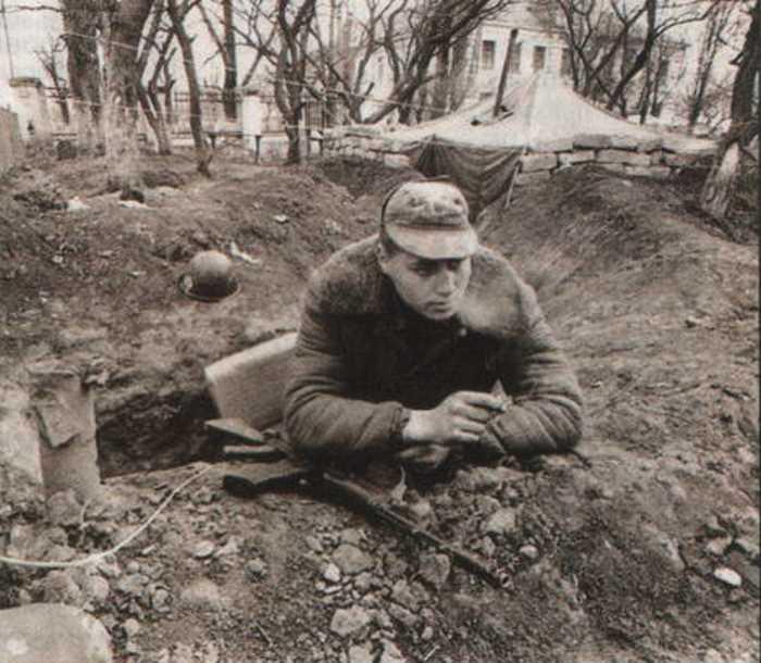 Боец 5-го Президентского полка ОДОН в окопе. Позади него — 45-я средняя школа, где, как говорят, учился Дудаев