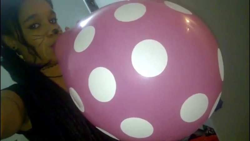 Cute cat girl blows and pops pink polka dotted balloon meow