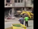 Building crashes down into a loader, lifting it off its wheels.