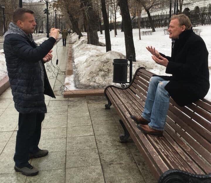 Взобравшись с ногами на лавку, артист рассуждает, какая Россия грязная и варварская страна.