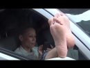 Beautiful woman sitting in a car with a phone, exposing her feet out of the window