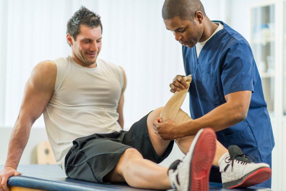 Спортсмен, получающий реабилитационную помощь при спортивной травме.