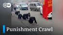 Chinese workers forced to go on punishment crawl on streets | DW News