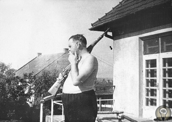 На фото комендант концлагеря Амон Гёт на балконе своей виллы готовится стрелять из винтовки по заключенным