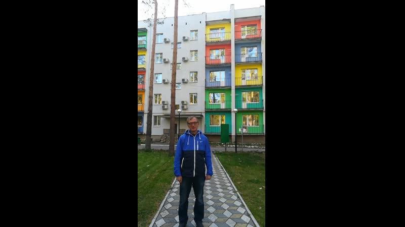 Алексей стоит рядом с административным корпусом в загородном комплексе имени Константина Эдуардовича Циолковского.