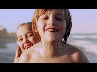 Stock-footage-little-girl-runs-up-the-beach-and-surprises-her-brother-with-a-big