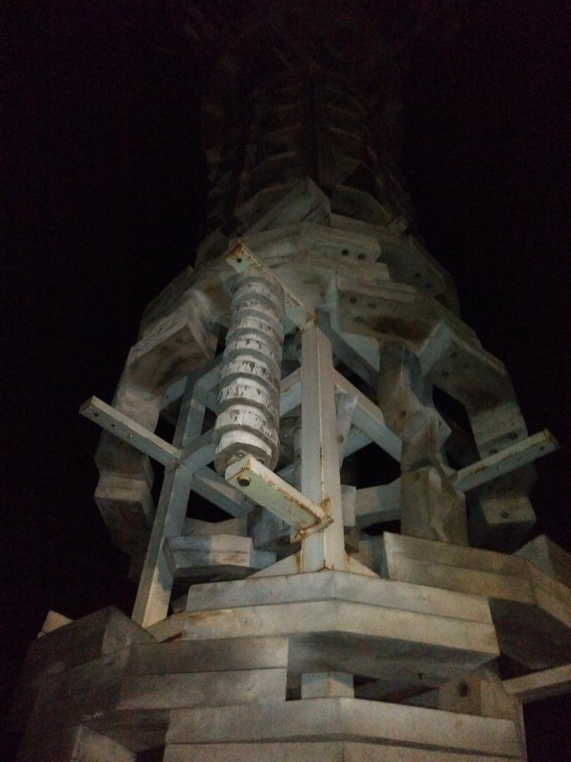 Огромная, с пятиэтажный дом, арка о четырёх столбах. Каждый столб — причудливое, а-почему-бы-и-нетное нагромождение дерева и металла (крыша теряется в высокой темноте, не удалось сфотографировать).