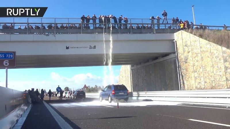 В Италии фермеры выливают молоко на проезжающие под мостом автомобили в знак протеста