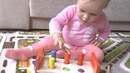 Алиса играет в деревянную развивающую игрушку для малышей