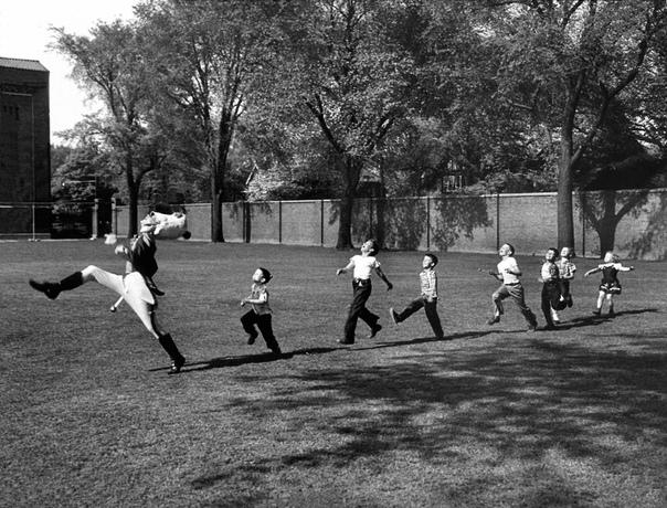 Барабанщик в униформе из Университета Мичигана отрабатывает марш, а семь детей пытаются скопировать его технику (1950 год