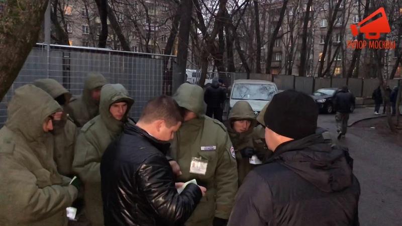 Сотрудник Росгвардии проверяет удостоверения у охранников ЧОО «НЕОМАКС-СБ» на Ивана Франко в Москве