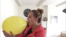 Sexy Girl blows up an enormous yellow balloon until it pops
