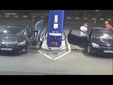 Gas station worker uses fire extinguisher on a smoking man