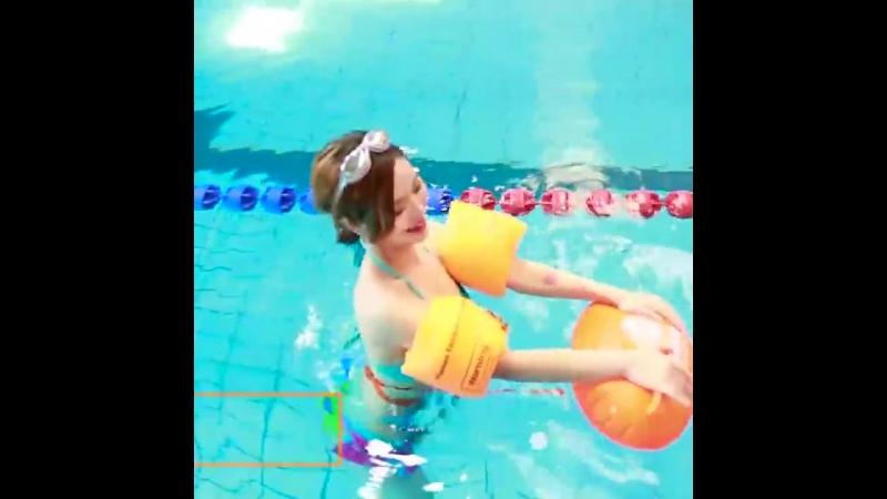 Asian girl wearing floaties in public bath.