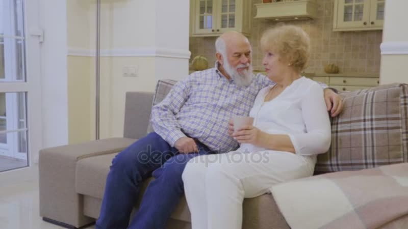 Старший мужчина с пожилой женщиной сидит на диване у себя дома разговаривает и расслабляется