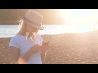 Beautiful blonde girl in a hat types a message on her mobile phone on the beach at sunset.