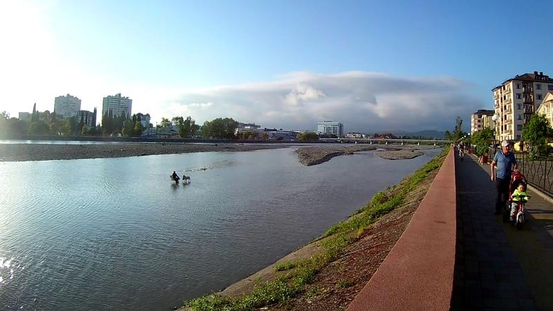 Центр Адлера, река Мзымта, сидит мужик посередине реки на стуле и рыбачит, рядом стоят 2 долматинца)